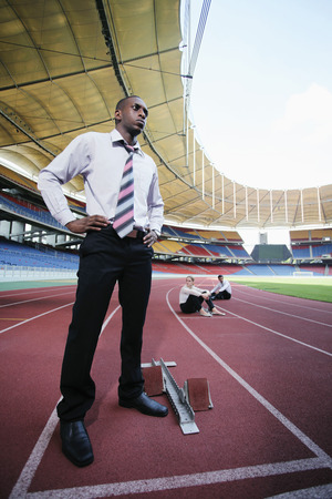 afro arab: Businessman standing on running track with arms akimbo