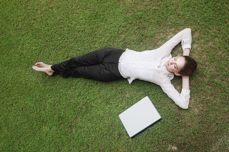 Businesswoman lying on the field with laptop beside her photo