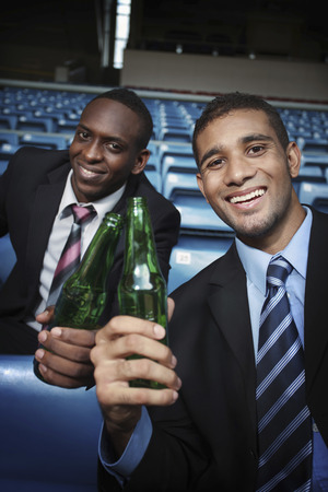 south western european descent: Businessmen drinking beer in stadium