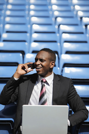 afro arab: Businessman talking on the phone while using laptop in stadium