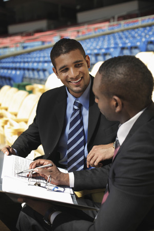 south western european descent: Businessmen having discussion in a stadium Stock Photo