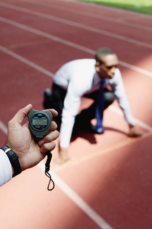 afro arab: Hand with stopwatch, businessman crouching on starting line in the background Stock Photo