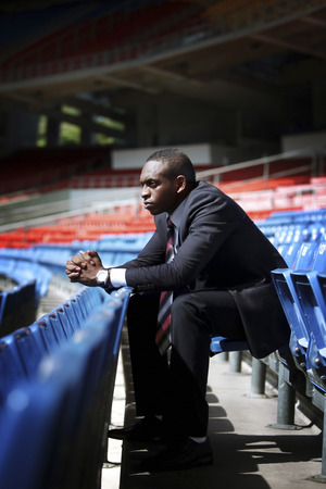 afro arab: Businessman sitting in empty stadium Stock Photo