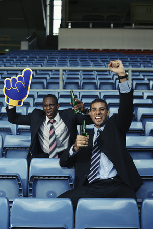 south western european descent: Businessmen drinking beer and cheering in stadium