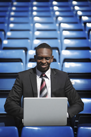afro arab: Businessman using laptop in stadium