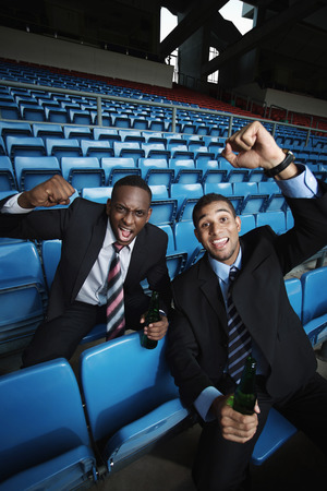 south western european descent: Businessmen drinking and cheering in stadium
