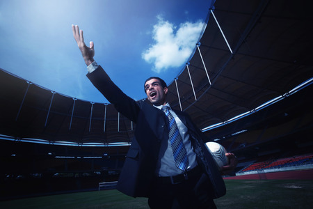 Businessman holding soccer ball and raising his hand photo