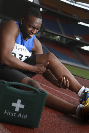 afro arab: Male athlete lying on track, clasping leg in pain