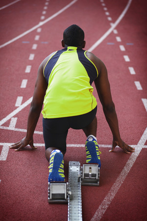 afro arab: Male athlete crouching on starting line