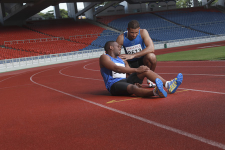 south western european descent: Male athlete laying on track, clasping leg in pain, another athlete helping Stock Photo