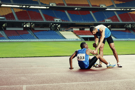 Male athlete laying on track, clasping leg in pain, another athlete helping Stock Photo