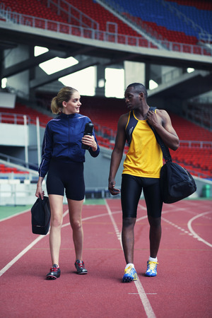 afro arab: Man and woman chatting while walking on track Stock Photo