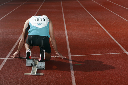 south western european descent: Male athlete crouching on starting line