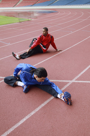 Athletes warming up on running track photo