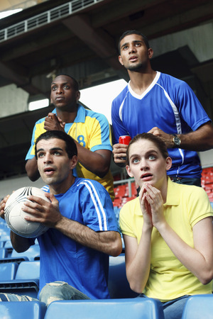 south western european descent: Men and woman watching soccer match in stadium