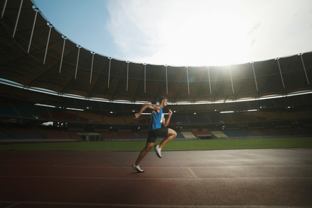 south western european descent: Man running on the track, warming up for a race  Stock Photo