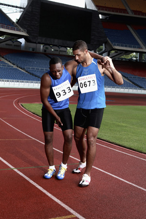 south western european descent: Male athlete helping another injured athlete