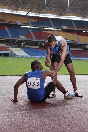 afro arab: Male athlete laying on track, clasping leg in pain, another athlete helping Stock Photo
