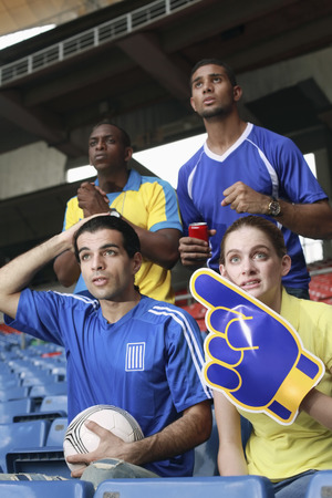south western european descent: Men and woman cheering in stadium