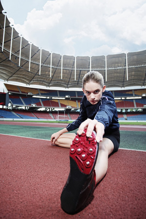 Female athlete warming up on running track photo