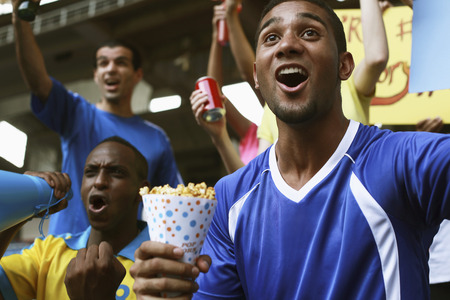 afro arab: Men cheering in stadium Stock Photo