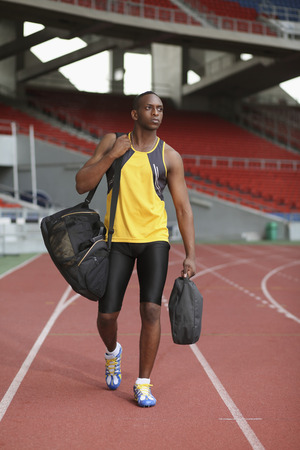 afro arab: Man walking on track, carrying bags Stock Photo