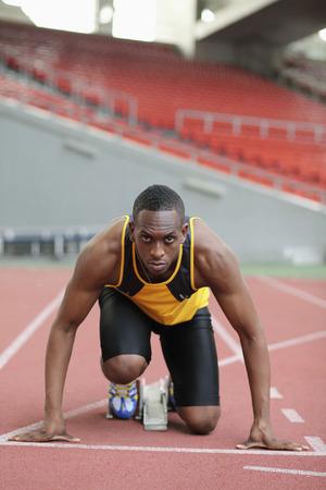 Male runner crouching on starting line