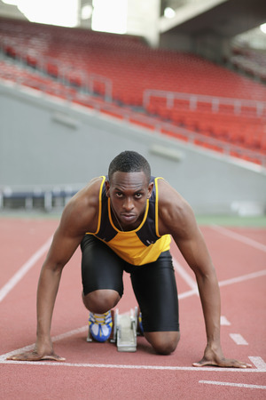 Male runner crouching on starting line