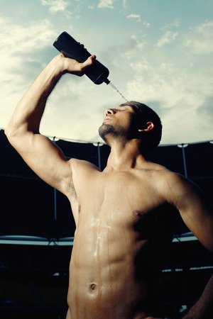 Male athlete pouring water over head photo