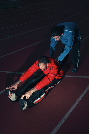 south western european descent: Sports coach helping male athlete stretching his body