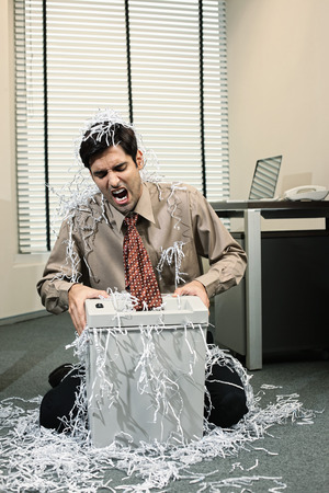 paper shredder: Businessman shouting whiles his tie getting caught in a paper shredder
