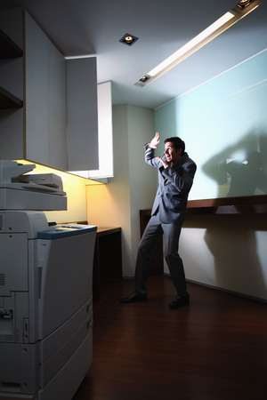 Businessman looking shockingly at a brightly illuminated filing cabinet photo