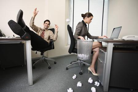 central european ethnicity: Empresaria con la computadora port�til y la celebraci�n de basura, hombre de negocios tirando papeles arrugados en todas partes Foto de archivo