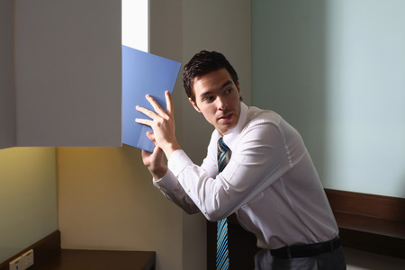Businessman stealing document from cabinet Stock Photo - 26388836