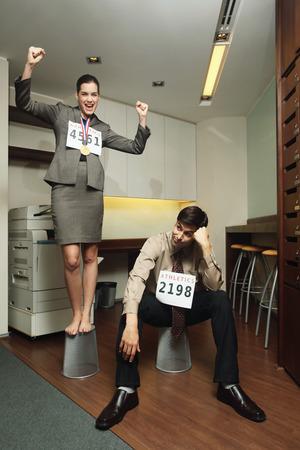 Businesswoman celebrating her success, businessman looking sad photo