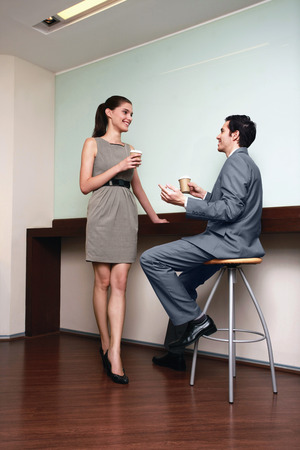 Businessman and businesswoman chatting in the office pantry Stock Photo