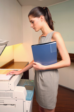 Businesswoman using photocopier Stock Photo