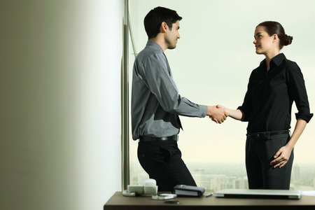 central european ethnicity: Businessman and businesswoman shaking hands