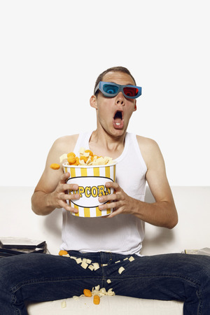 Man in 3D glasses looking shocked while watching television photo
