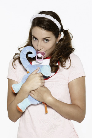 soother: Woman sucking on pacifier and hugging toy animal