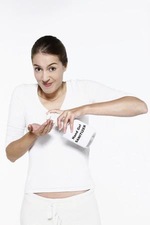 sanitizer: Woman using hand sanitizer Stock Photo