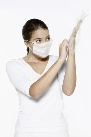 plastic glove: Woman putting on plastic glove Stock Photo