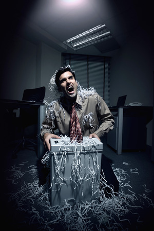 shredder: Businessman shouting whiles his tie getting caught in a paper shredder