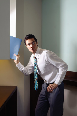 Businessman stealing document from cabinet Stock Photo - 26390907