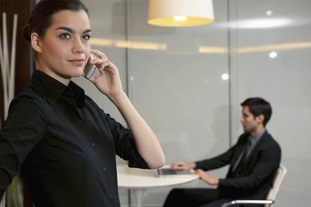 central european ethnicity: Mujer de negocios hablando por tel�fono, hombre de negocios usando la computadora port�til en el fondo Foto de archivo