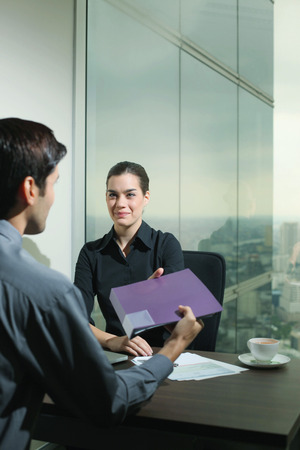 central european ethnicity: Businessman passing folder to businesswoman Stock Photo