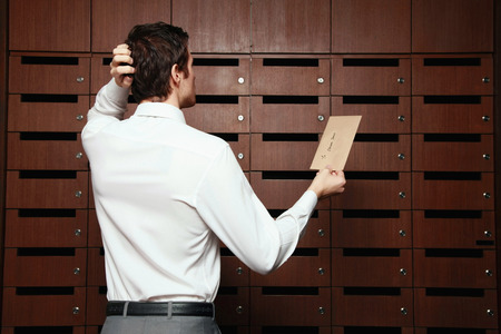Businessman scratching his head while looking at mail slots photo