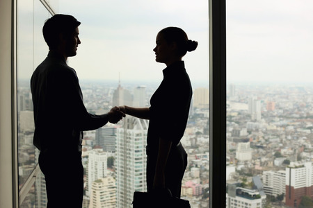 Silhouette of business people shaking hands photo