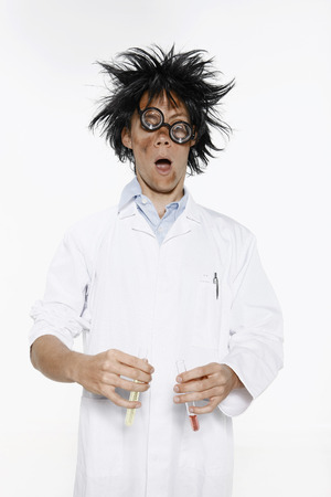 Man with hair and face in a mess holding test tubes of liquid