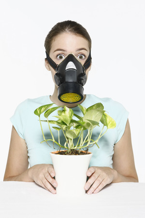 Woman with gas mask holding potted plant photo